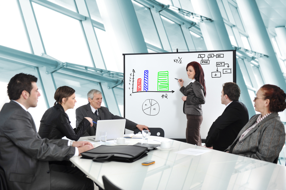Person on a whiteboard, presenting in front of a team.