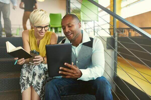 Two people sitting at the stairs, looking at a tablet.