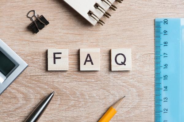 Image of desktop with FAQ written in wooden block letters.